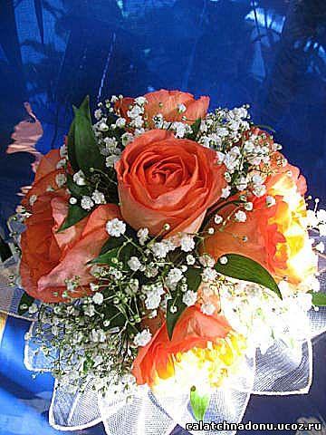 Свадебный букет из красных роз оформлен гипсофилой и рускусом